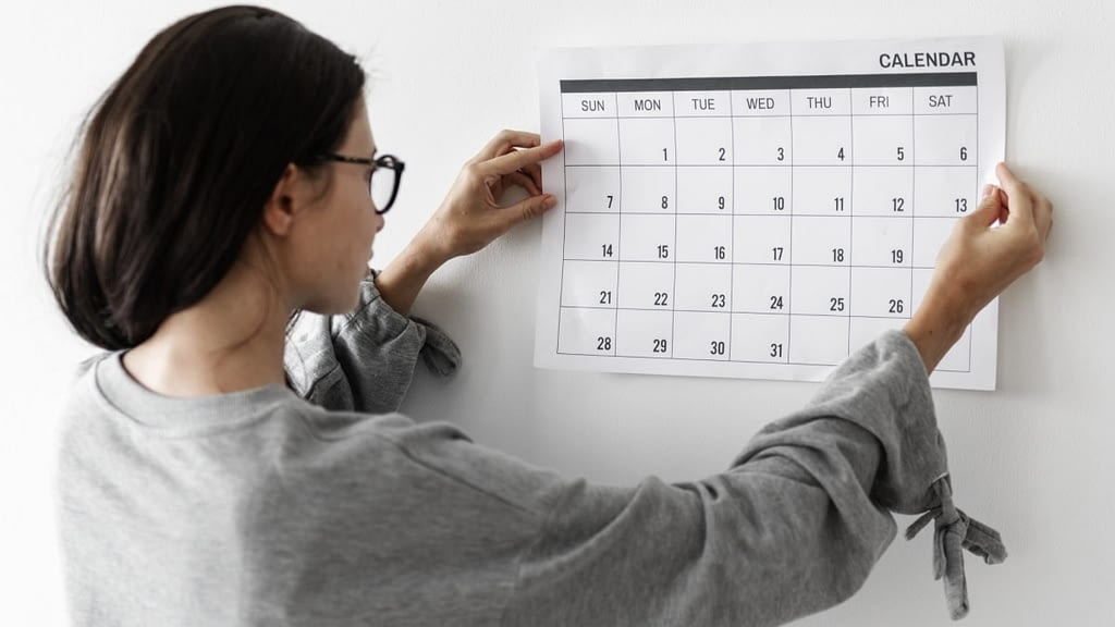 A photograph of a woman hanging a calendar on the wall.