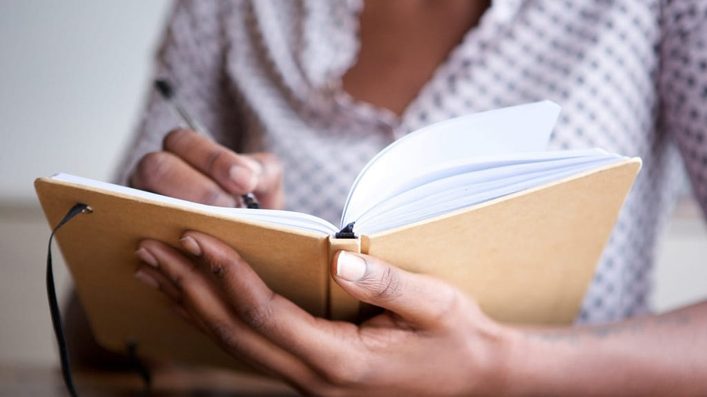 A photograph of a person writing in a notebook.