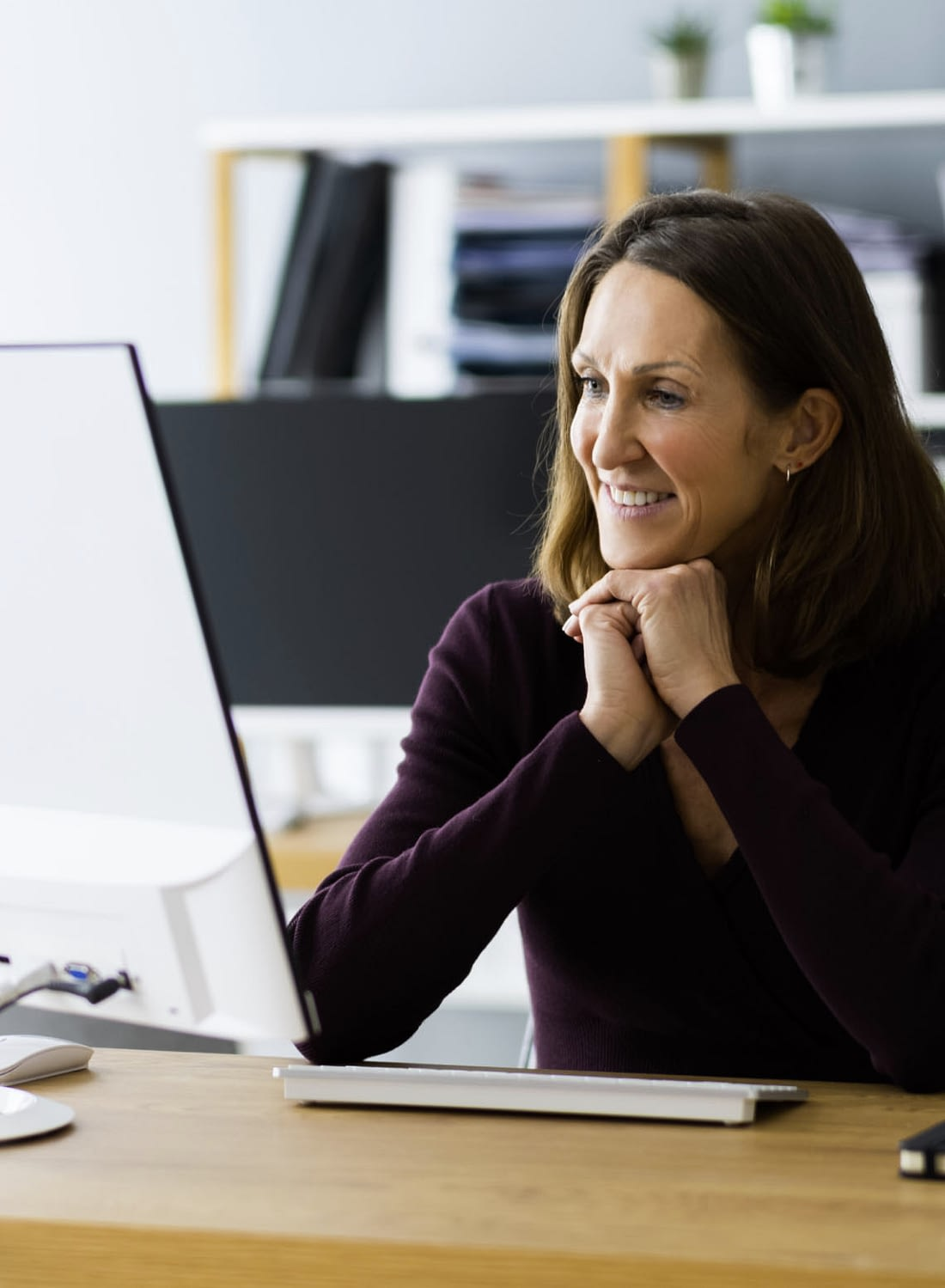 A photograph of a woman smiling at a computer screen.