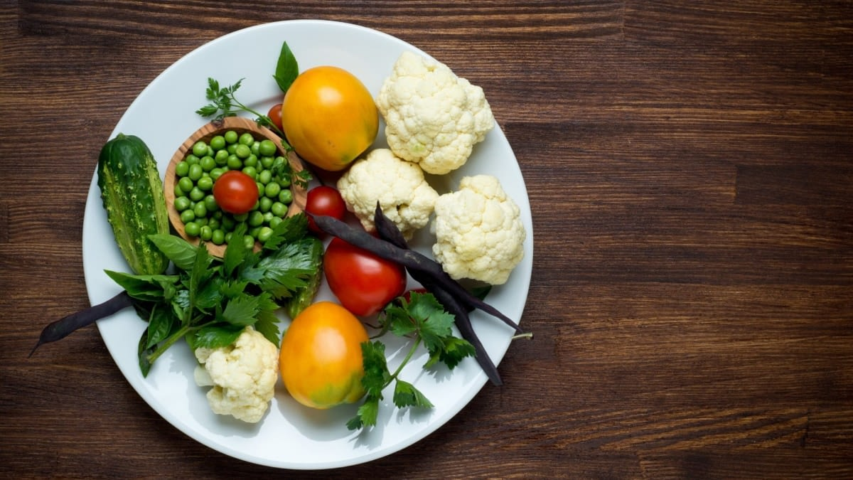A photograph of a plate of food with tomatoes, cauliflower, peas, a cucumber and fresh herbs.