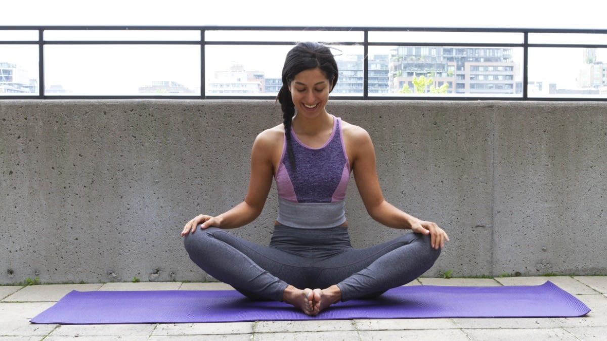 A photograph of a woman sitting on a yoga mat.