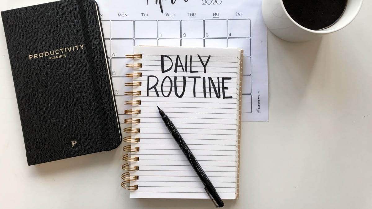 A photograph of a notebook with the text Daily Routine. Next to it is a Productivity planner.