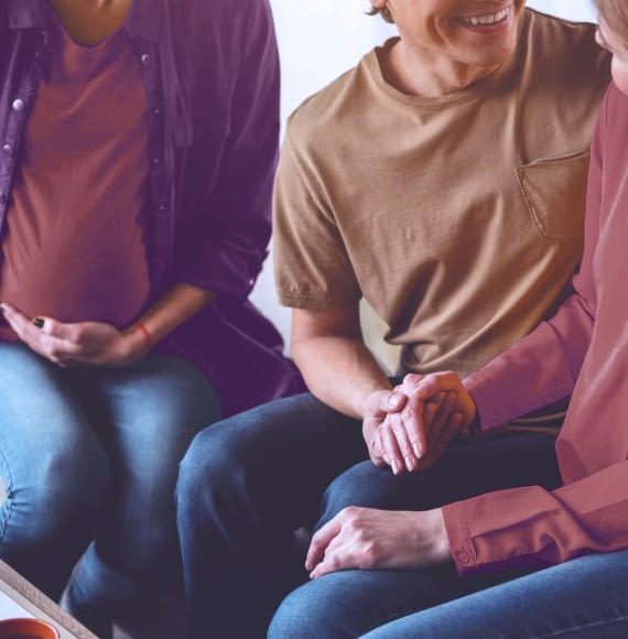 A photograph of a pregnant woman sitting beside another couple holding hands.